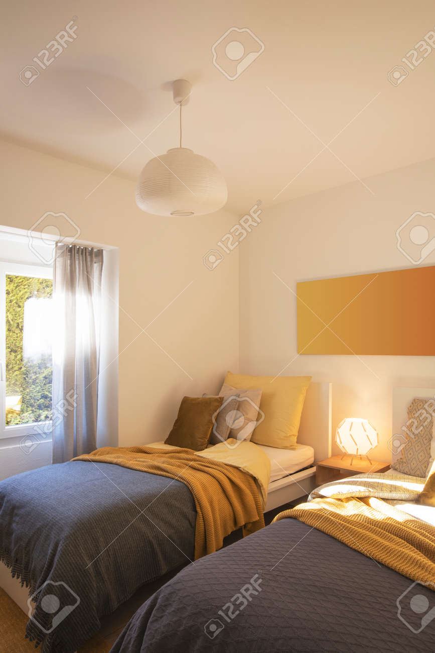 Modern bedroom with two singles beds with clean bed sheets and large pillow above. White wall. Nobody inside. - 163075635