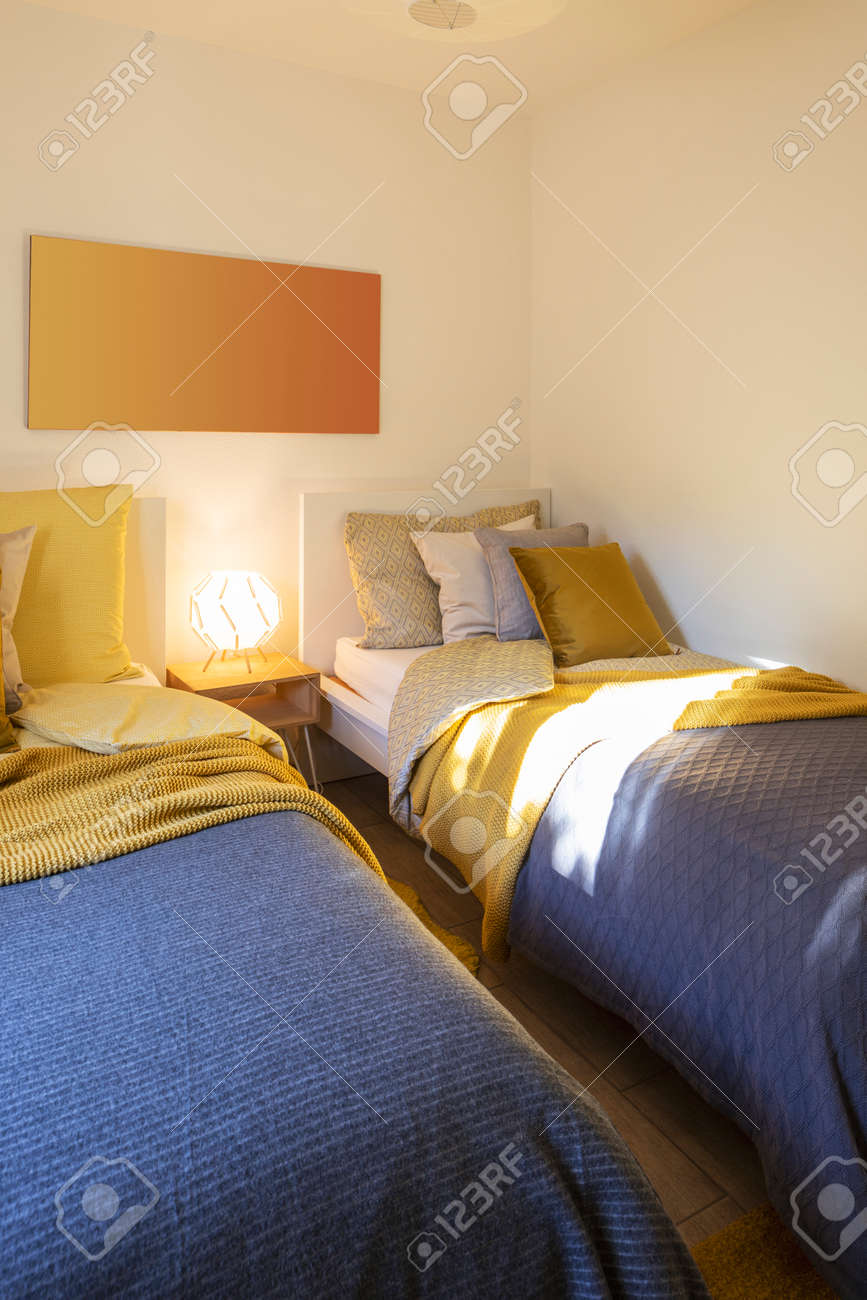 Modern bedroom with two singles beds with clean bed sheets and large pillow above. White wall. Nobody inside. - 163075636