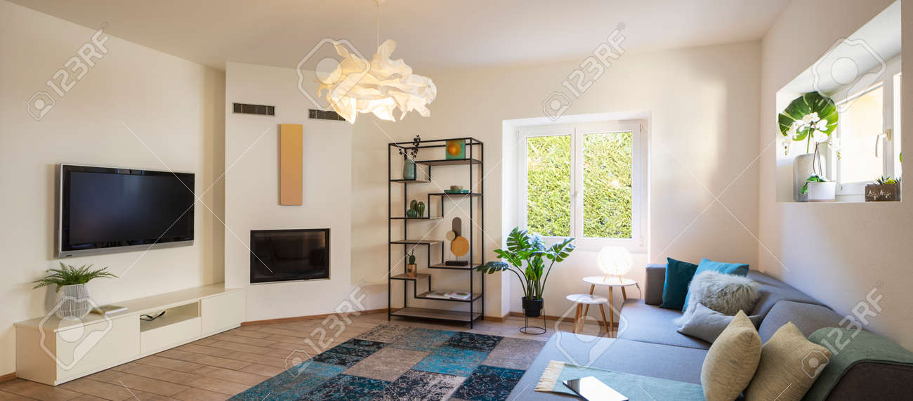 Panorama of wide modern living room with design sofa and large pillows above. Design library and small fireplace. Nobody inside - 163075637