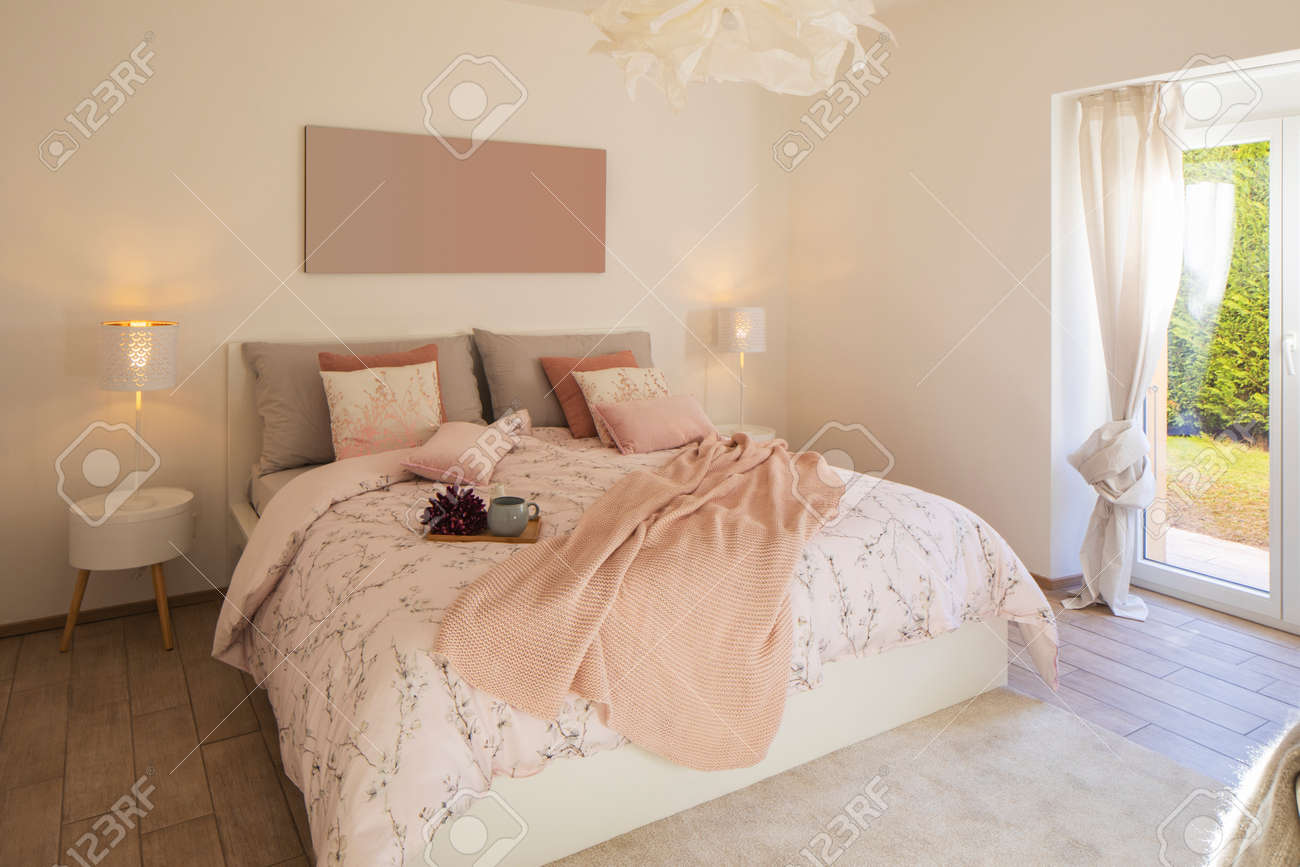 Modern, bright and luxury bedroom in design apartament. Fresh bed sheets and pillows above. There's a tray with a cup for breakfast. - 163078106