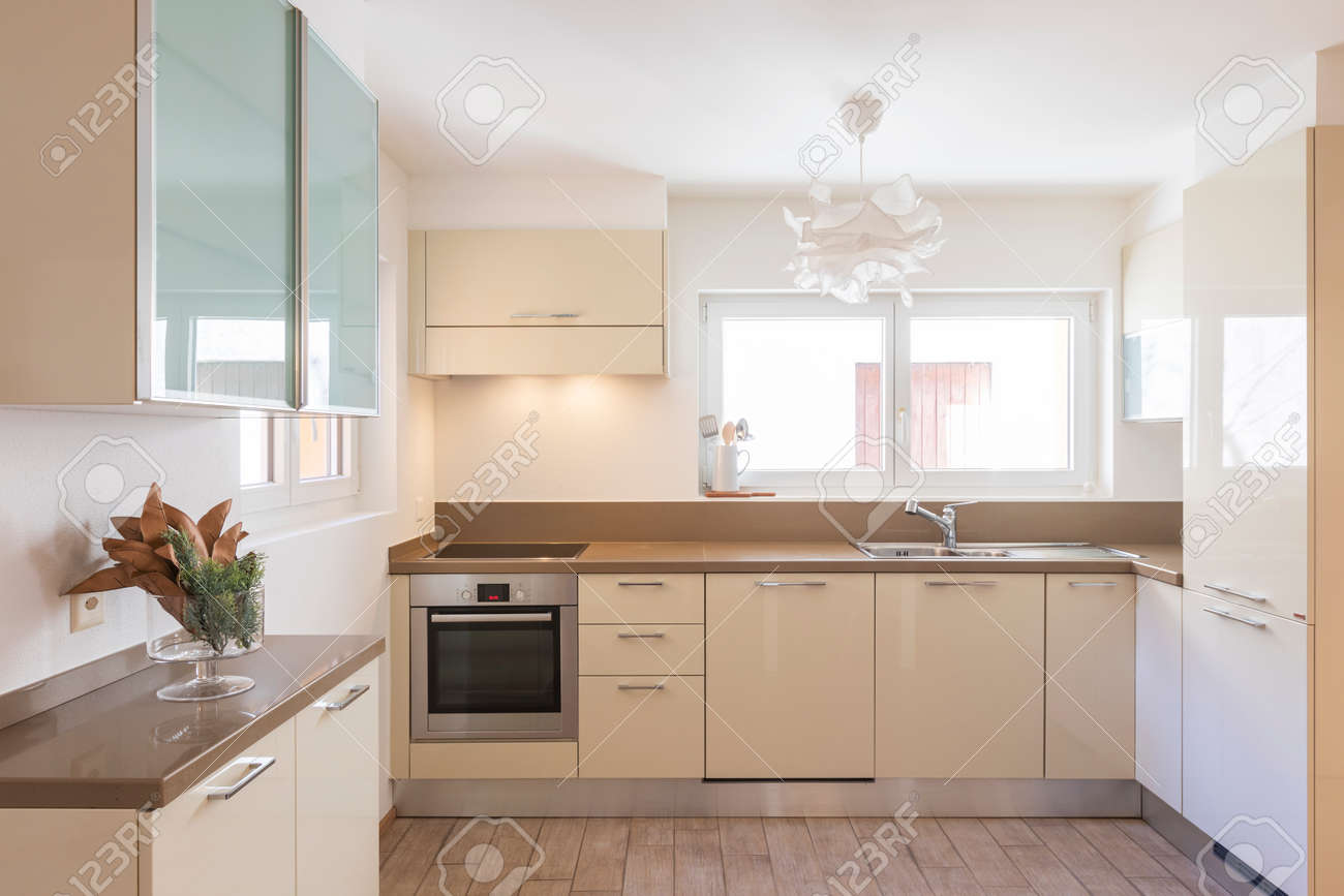 Clean and modern cream kitchen with large and bright windows. Nobody inside - 163078112