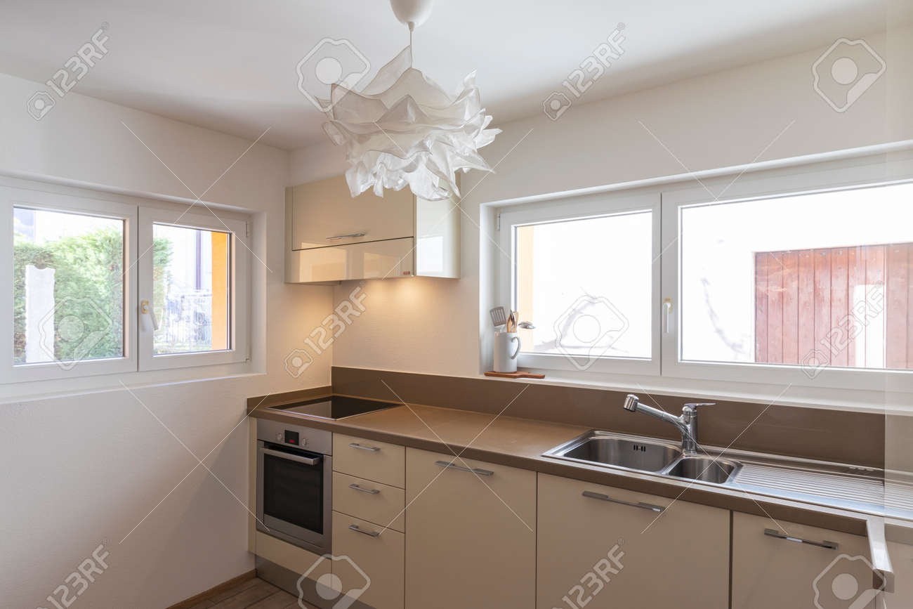 Clean and modern cream kitchen with large and bright windows. Nobody inside - 163079134