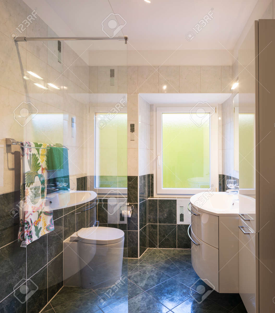 Bathroom with glass shower, tiles green and white. Large bright windows. Nobody inside. - 163079136