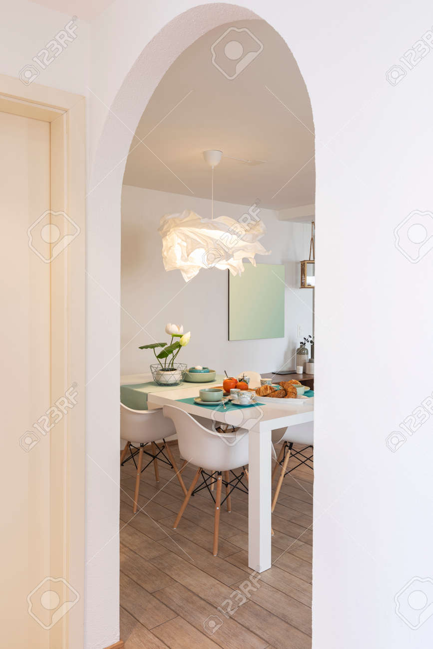 Detail from hallway of elegant and romantic white table ready for breakfast with brioche, cups for coffee and fruits. Nobody inside - 163079139