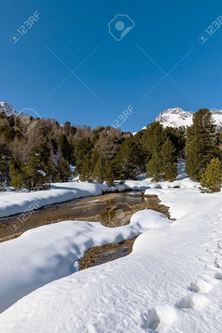 Panorama with lots of snow on Lukmanier in Ticino, on the Swiss Alps and a romantic stream through the landscape. Nobody inside - 165367470