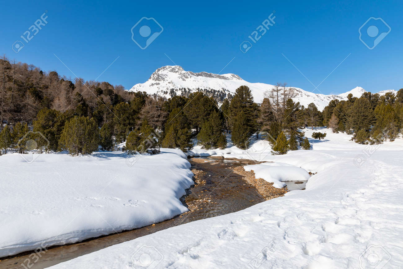 Panorama with lots of snow on Lukmanier in Ticino, on the Swiss Alps and a romantic stream through the landscape. Nobody inside - 165589881