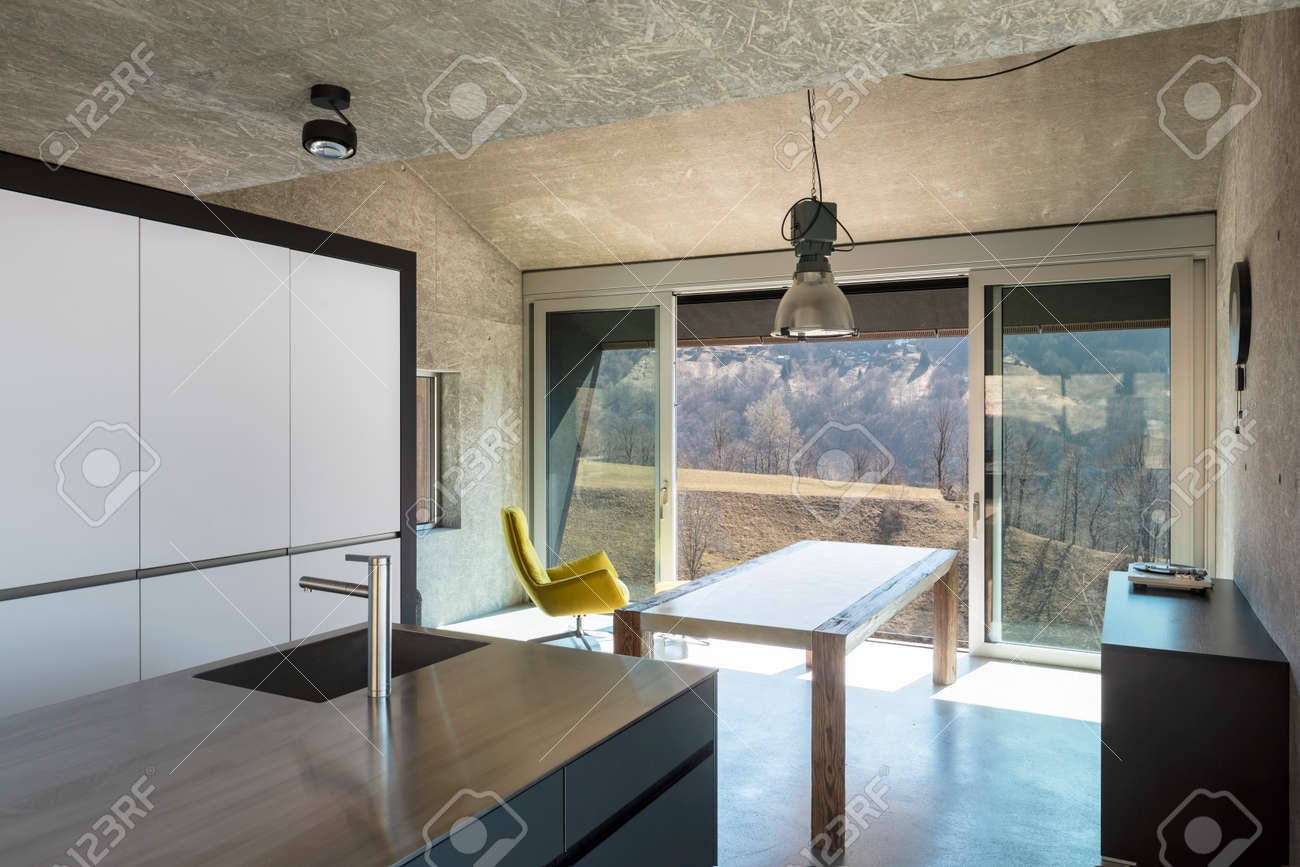 Detail of modern kitchen island, sink. Interior of a beautiful modern house, with a table, a yellow armchair and a view of nature. None inside - 166417750