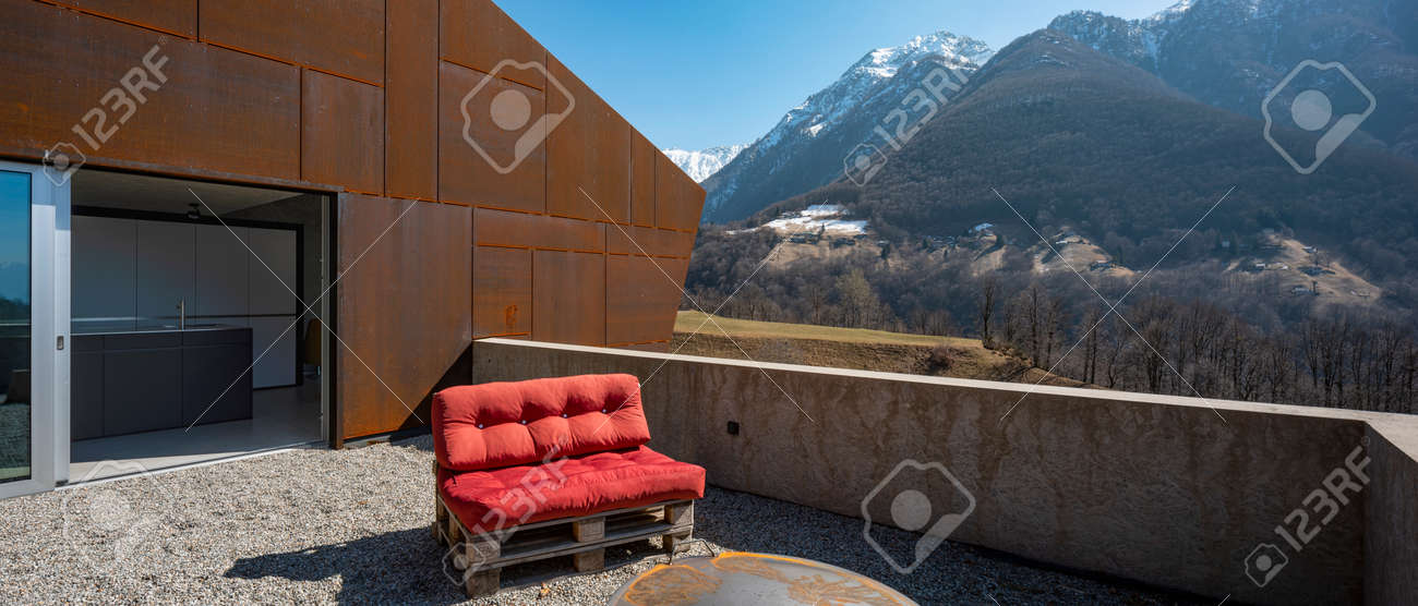 Modern house exteriors with veranda. Red sofa overlooking the mountains of Switzerland. Concept, nobody inside - 166390035