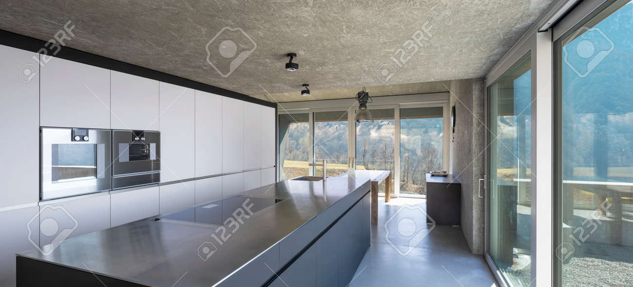 Modern white kitchen with large island, induction hob, two ovens, sink and stainless steel top. Large windows overlooking the nature of Switzerland. Nobody inside - 166417753