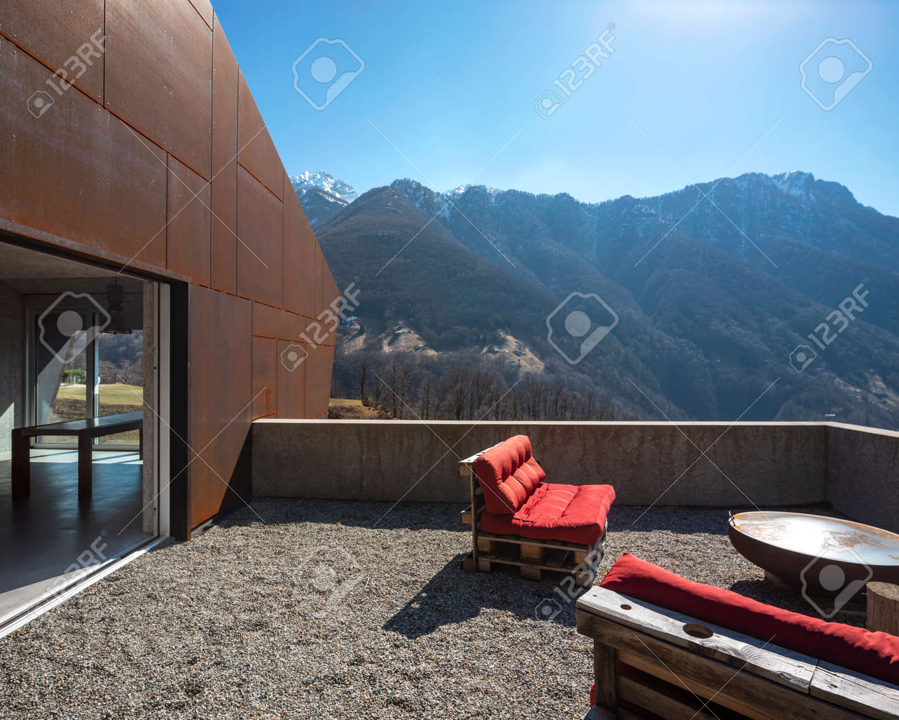 Modern house exteriors with veranda. Red sofa overlooking the mountains of Switzerland. Concept, nobody inside - 166417754