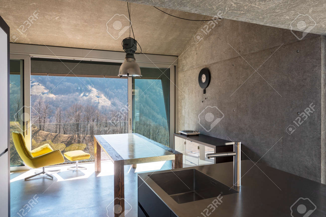 Detail of modern kitchen island, sink. Interior of a beautiful modern house, with a table, a yellow armchair and a view of nature. Nobody inside - 166417757
