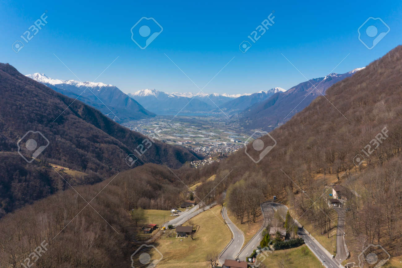 Aerial view of the Morobbia Valley, winter landscape on a sunny day with snow on the mountains. At the bottom of the valley you can see the Magadino plain and the Locarno lake - 166495226
