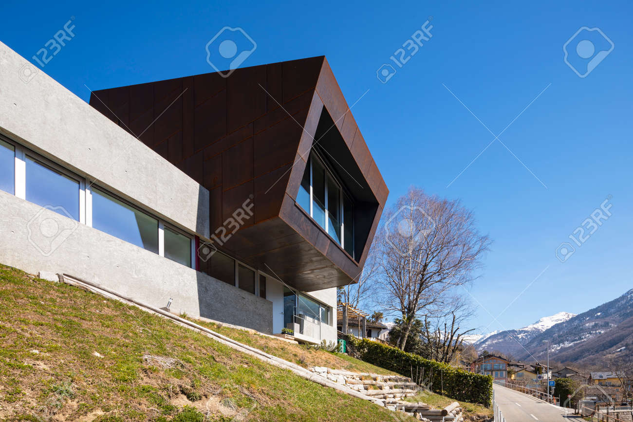 Exterior modern isolated villa, surrounded by nature. Iron and concrete cladding. Nobody inside - 166462729