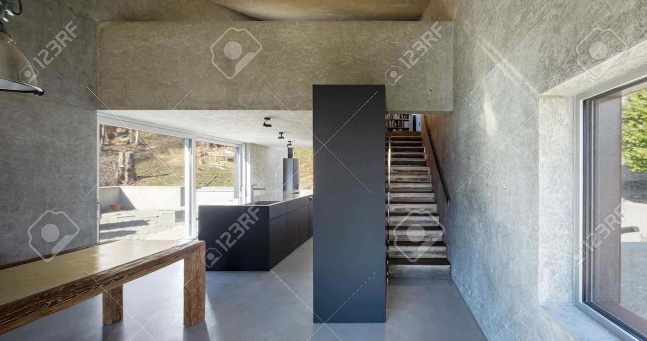 Front view of open space in modern villa with kitchen, minimal stairs and table. Large windows. Nobody inside - 166495247