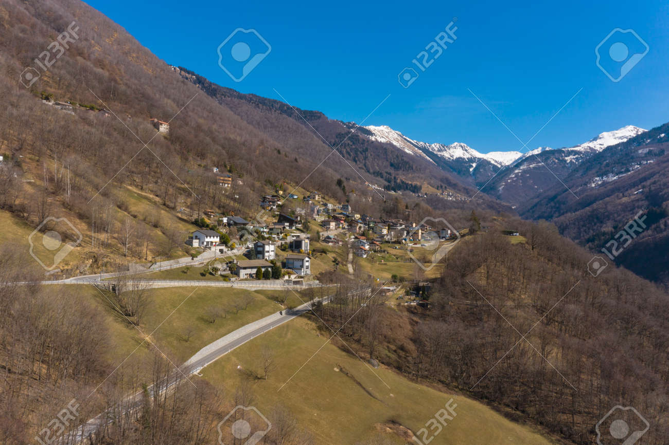 Aerial view of the Morobbia Valley, winter landscape on a sunny day with snow on the mountains. Blue sky - 166495251