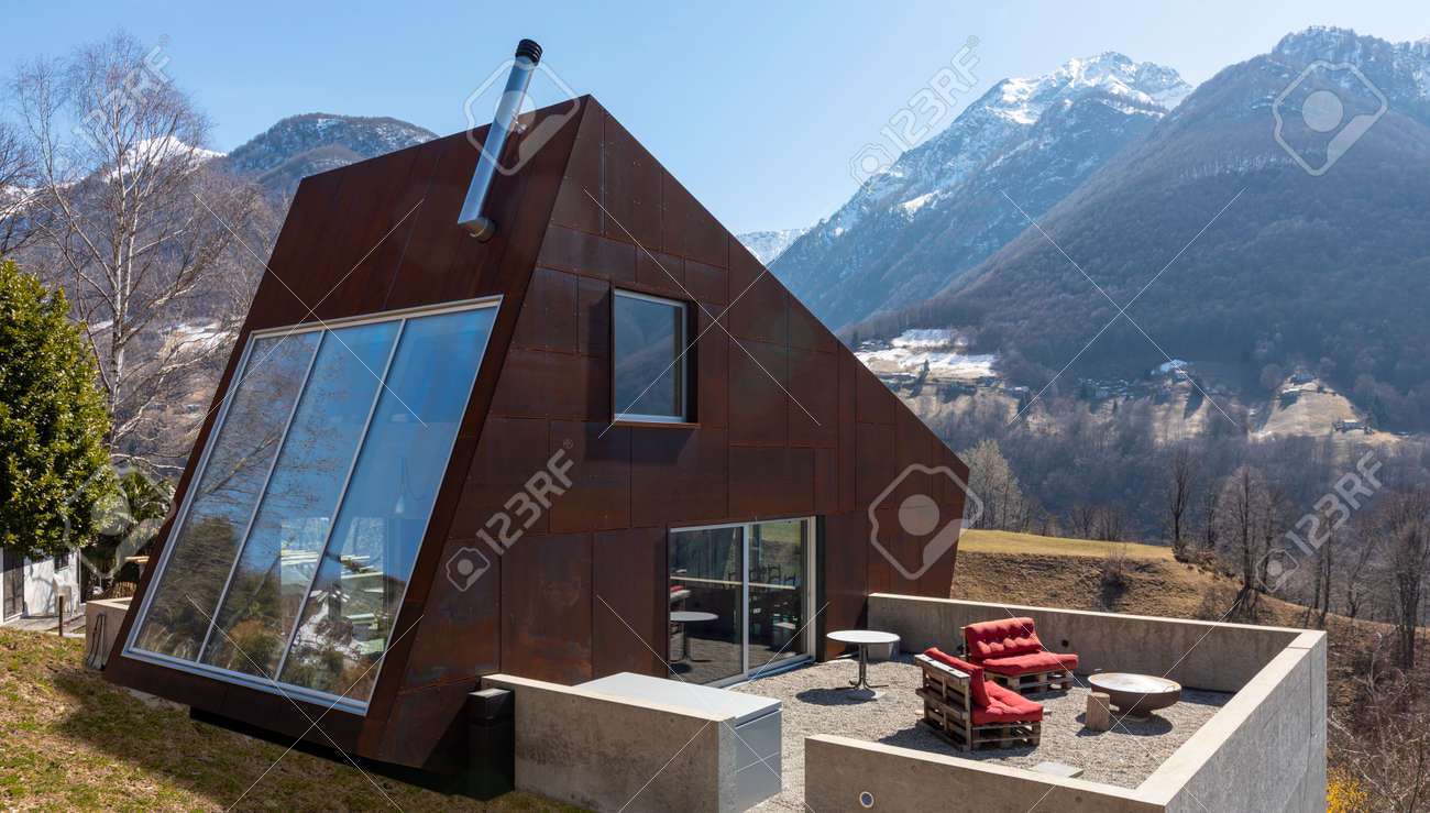 Back exterior of modern isolated villa with garden, surrounded by nature. Beautiful landscape of Swiss Alps. Nobody inside - 166826265