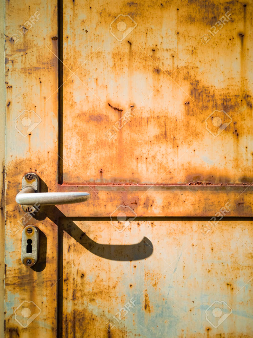 Detail of a rusty door of a factory. Frontal view. Nobody inside. Copy space - 170380072
