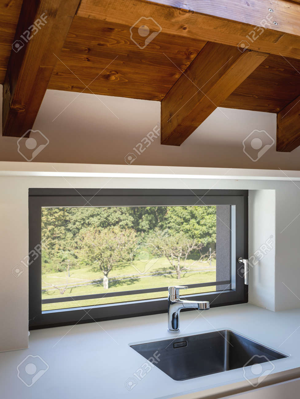 Modern white kitchen detail with steel sink and window overlooking nature. Natural light - 167299064