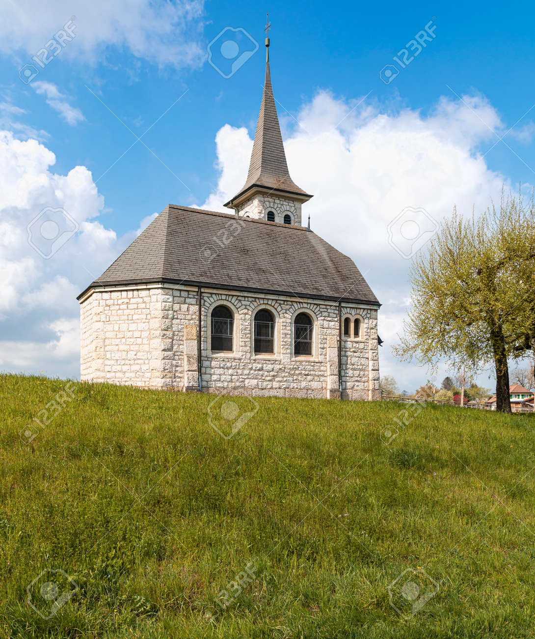 Characteristic church in the green field in the Swiss Alps of the Canton Jura. Nobody inside. Cloudy day. - 170380017