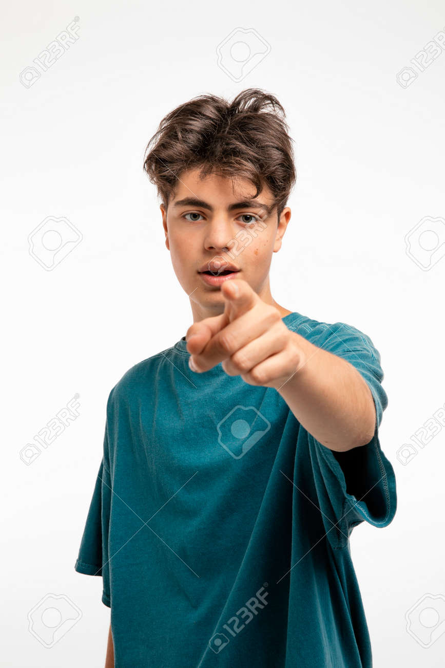 Portrait of teenager on white background in studio. The boy is standing and pointing with his finger at you who are standing in front of him - 170379907
