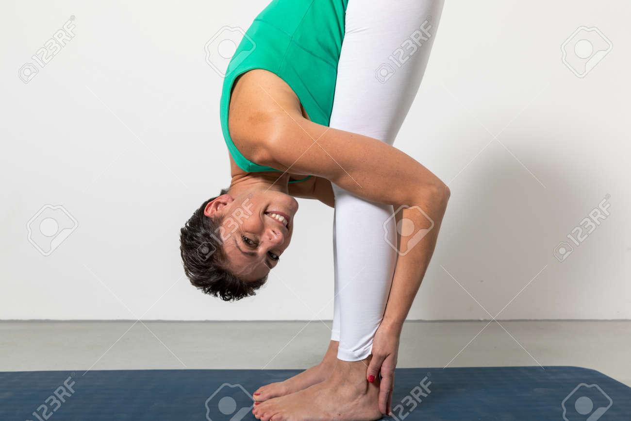 uttanasana, woman in forward pose position on white background - 170379831