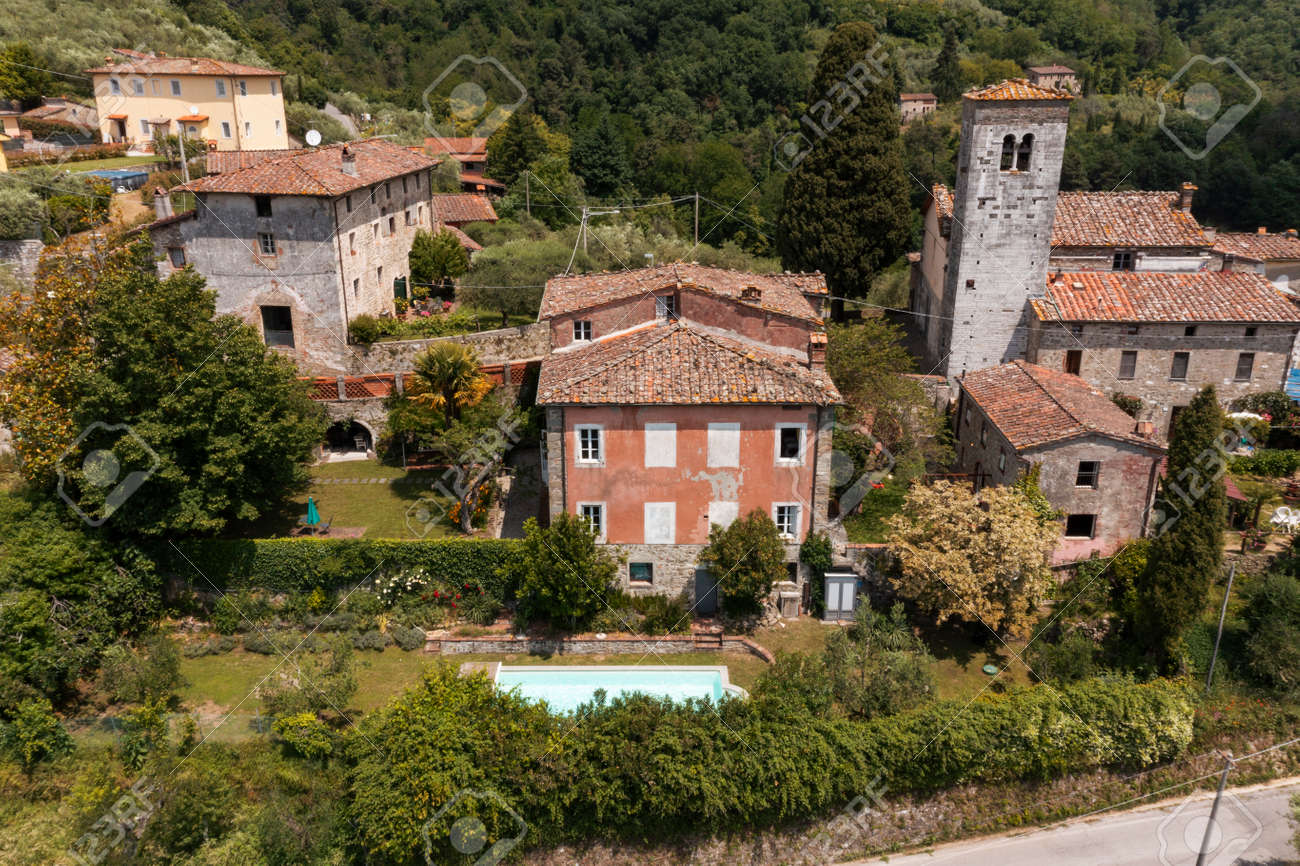 House or cottage in the middle of summer with a beautiful garden and swimming pool in Tuscany. The place is romantic and makes you dream. The shot was done with a drone. Italy always beautiful - 171317453