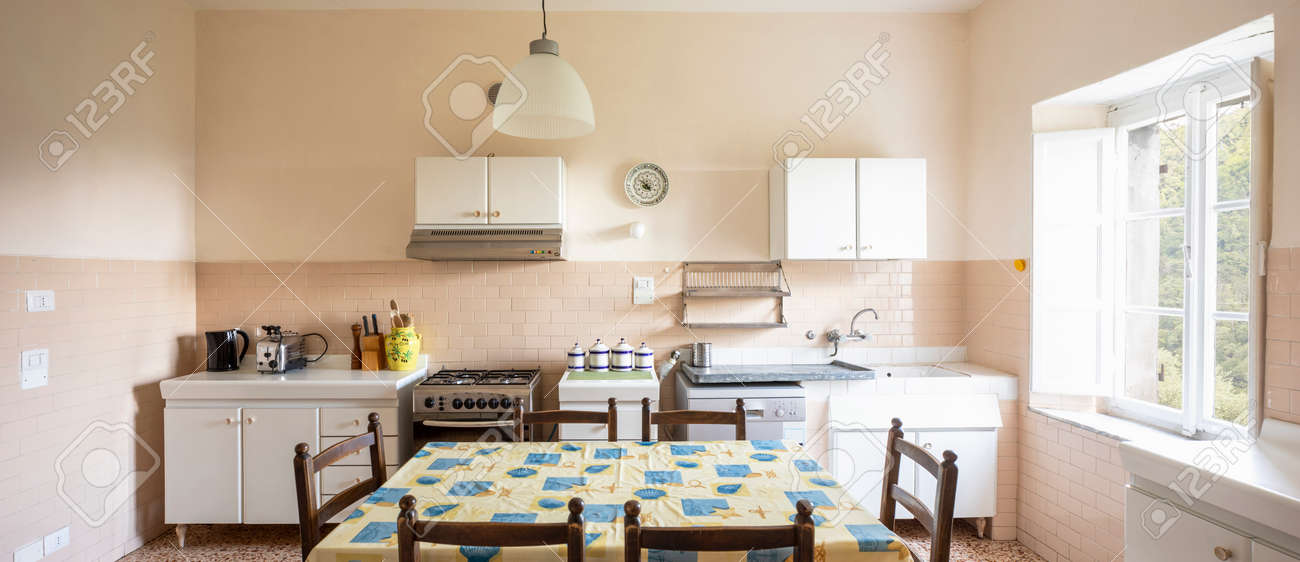 Interior of an old kitchen, almost antique, a table in the middle, the space is large and it is also bright. There is no style, they are pieces of furniture put together without aesthetic taste and the whole form romanticism - 171301157