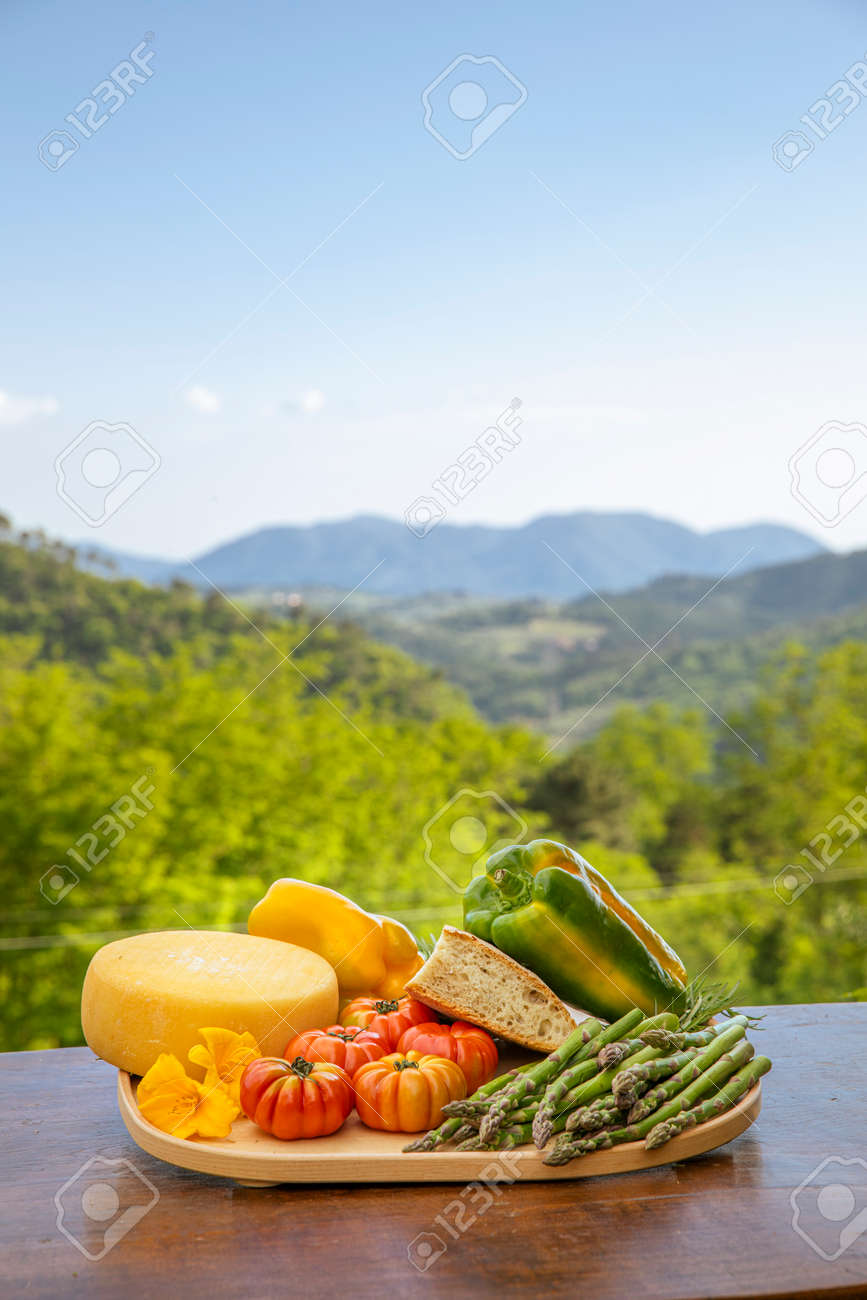 Plank of wood full of food from the land of Tuscany in Italy, peppers, salami, tomatoes. View on the Italian nature full of green plants. - 171317483