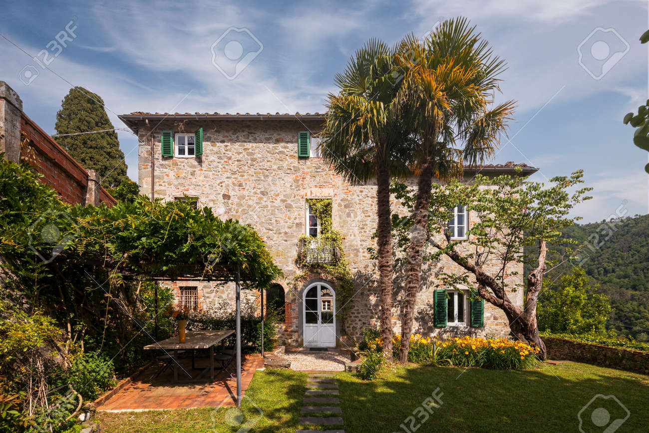 Beautiful Italian farmhouse in Tuscany surrounded by nature with a large garden. The season is summer and the sun is shining. - 171317496