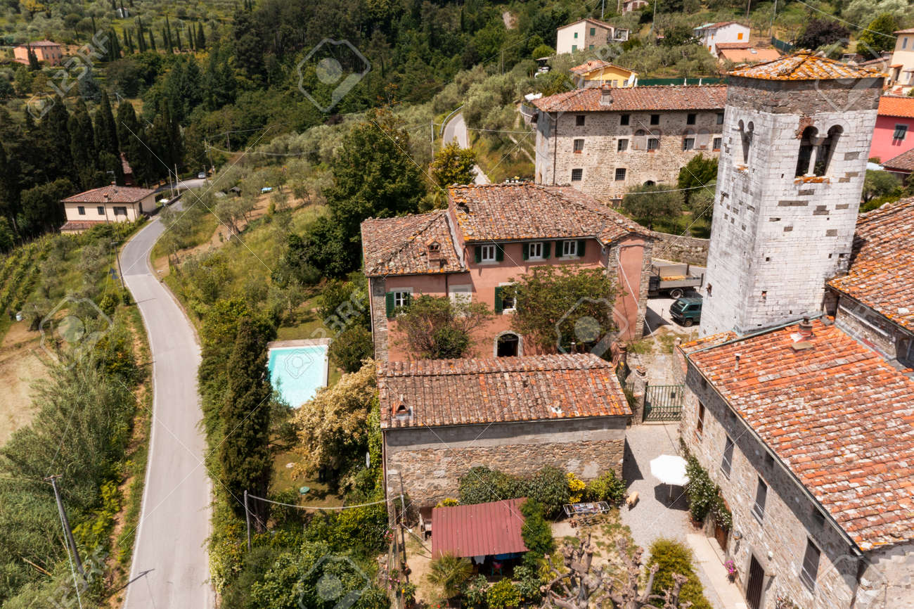 House or cottage in the middle of summer with a beautiful garden and swimming pool in Tuscany. The place is romantic and makes you dream. The shot was done with a drone. Italy always beautiful - 171332153