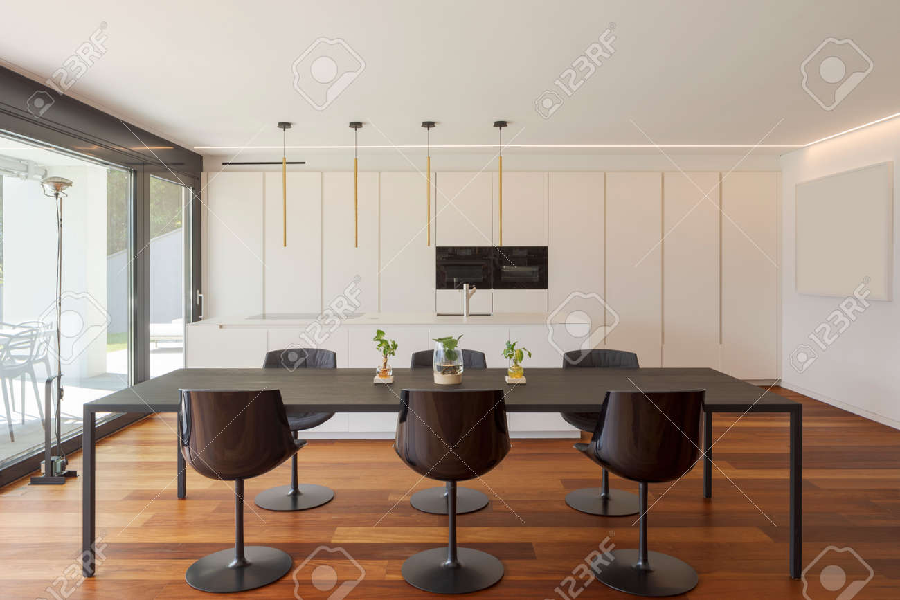 Interior of a modern apartment, with dining room and open kitchen. Front view hardwood floors. Nobody inside, the table seats six. - 171413191