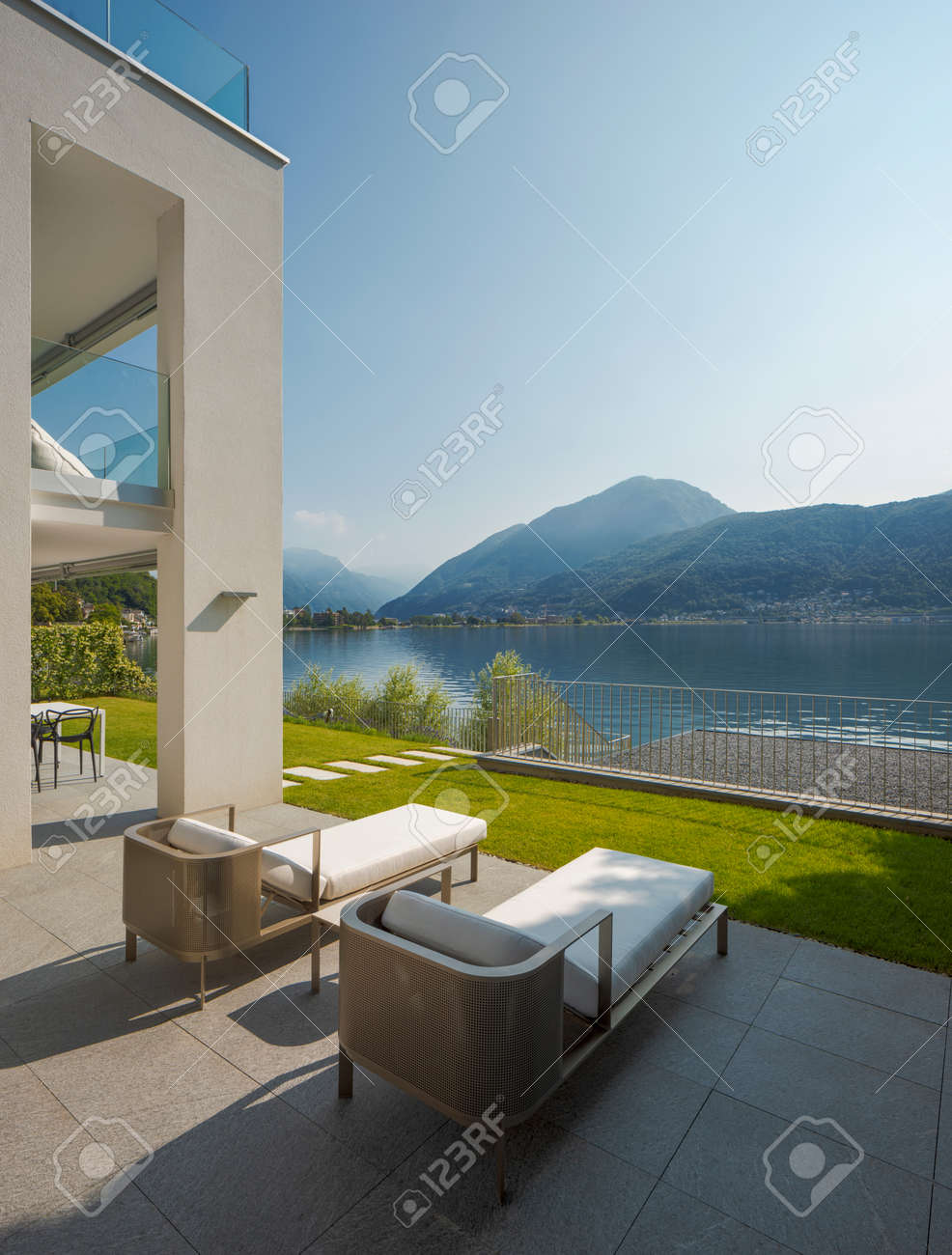 Detail of private terrace overlooking Lake Ceresio in Switzerland. Two deck chairs in the foreground. it's a sunny day and it's midsummer - 171413318