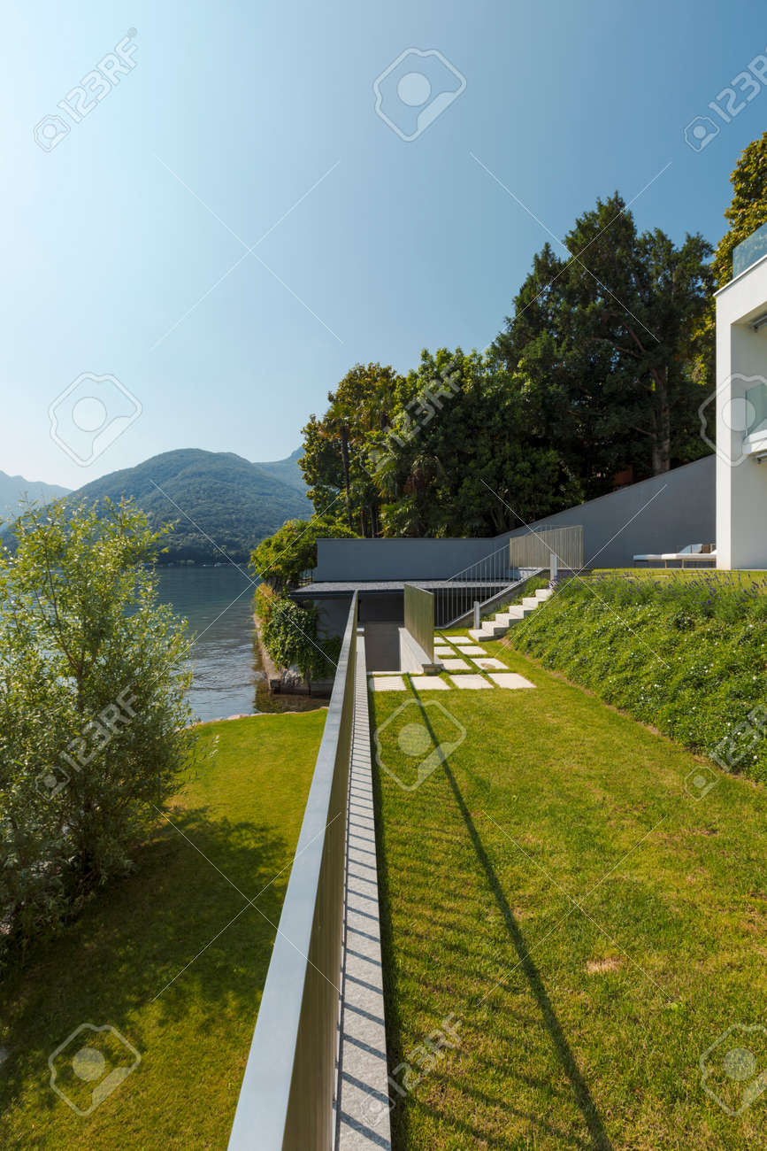Exterior of a modern house, the garden overlooks the lake. A landscape that gives a feeling of bliss. Nobody inside - 171413008