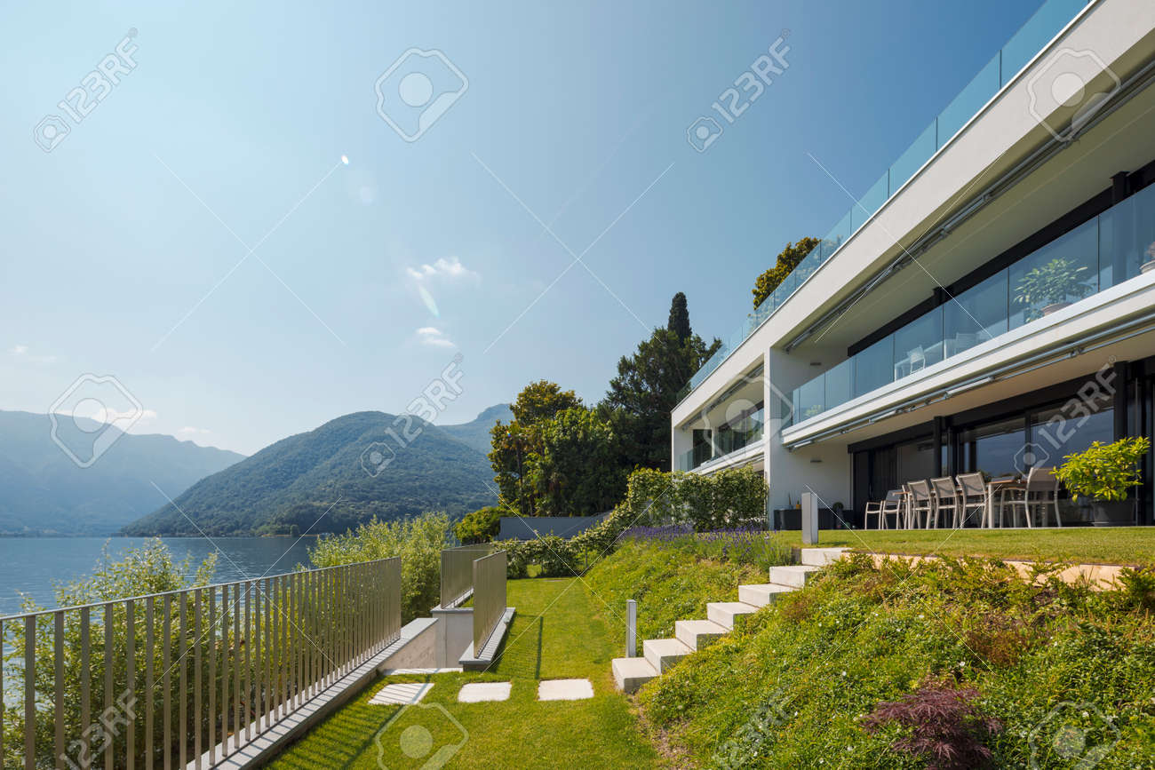 Modern house of two apartments with a beautiful garden directly on Lake Ceresio. Sunny day with blue sky. Minimalist and linear architecture. Panoramic view of the lake. Space for your text - 171413590