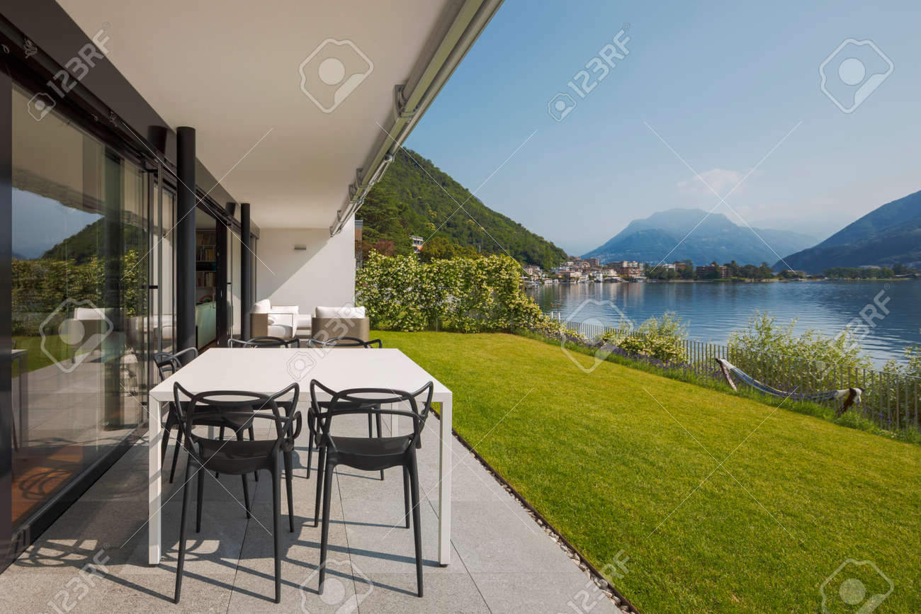 Modern house of two apartments with a beautiful garden directly on Lake Ceresio. Sunny day with blue sky. Minimalist and linear architecture. Panoramic view of the lake. Space for your text - 171413502