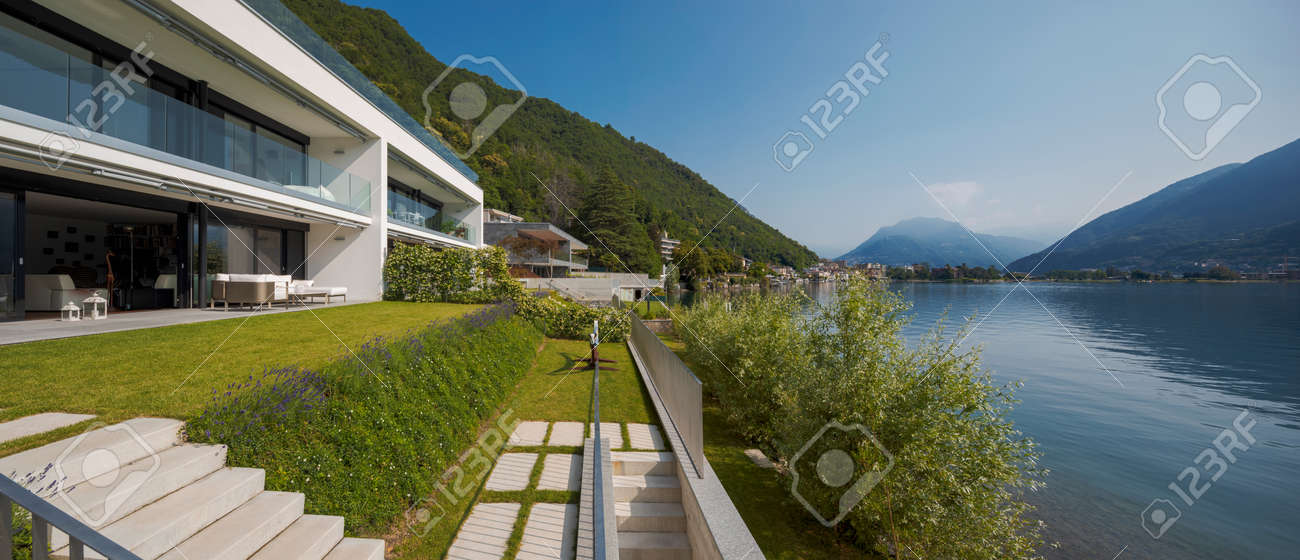 Modern house of two apartments with a beautiful garden directly on Lake Ceresio. Sunny day with blue sky. Minimalist and linear architecture. Panoramic view of the lake. Space for your text - 171413036