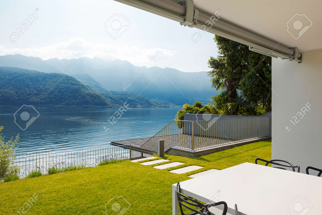 Private terrace overlooking Lake Ceresio in Switzerland. In front of a beautiful green lawn table and chairs. It's a sunny day and it's midsummer - 171412899