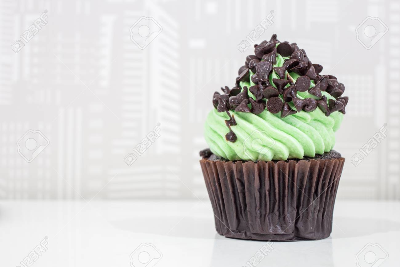 Green cupcakes with cream on top and Chocolate chip placed on the table - 81837267