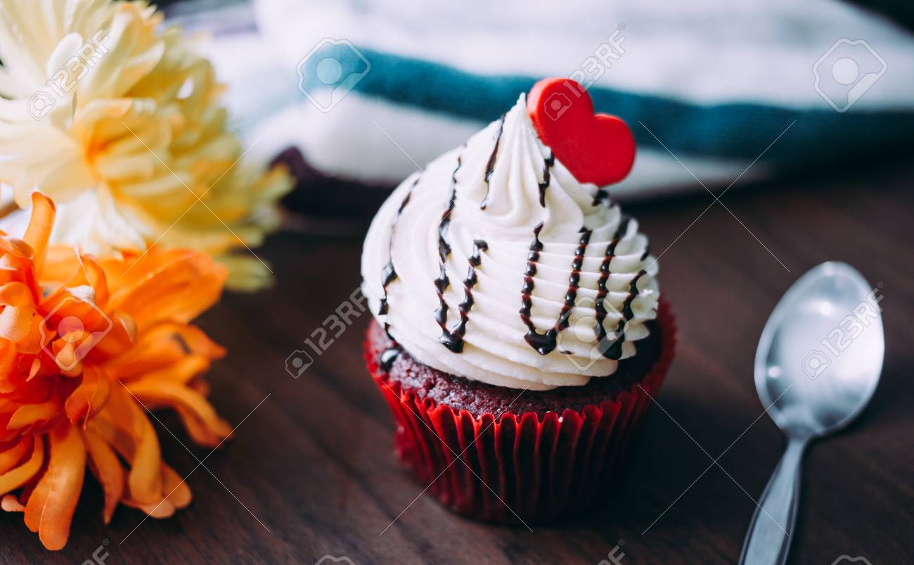 Red cupcakes with cream on top and heart-shaped sugar placed on the table near the window in the morning, vintage tone. - 81761021