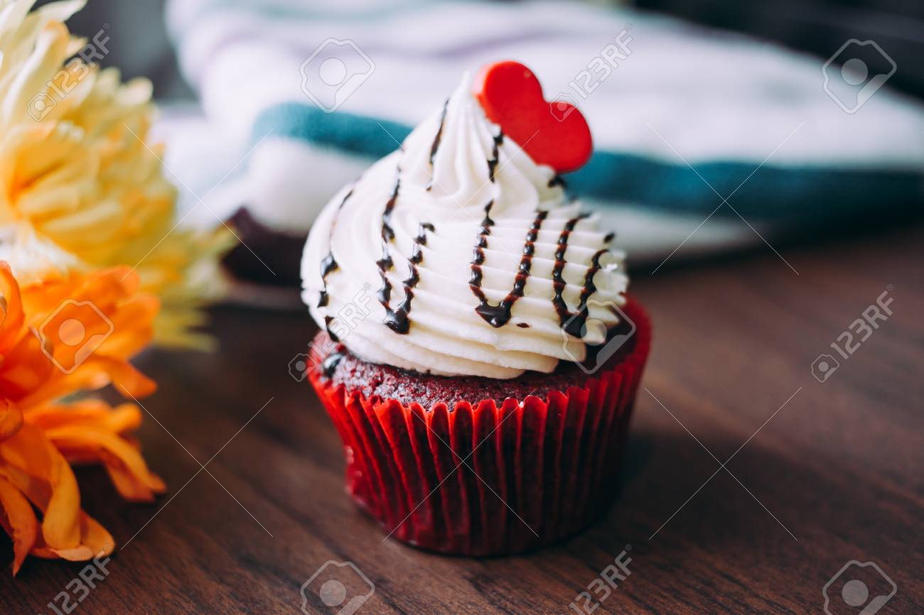Red cupcakes with cream on top and heart-shaped sugar placed on the table near the window in the morning, vintage tone. - 81761022