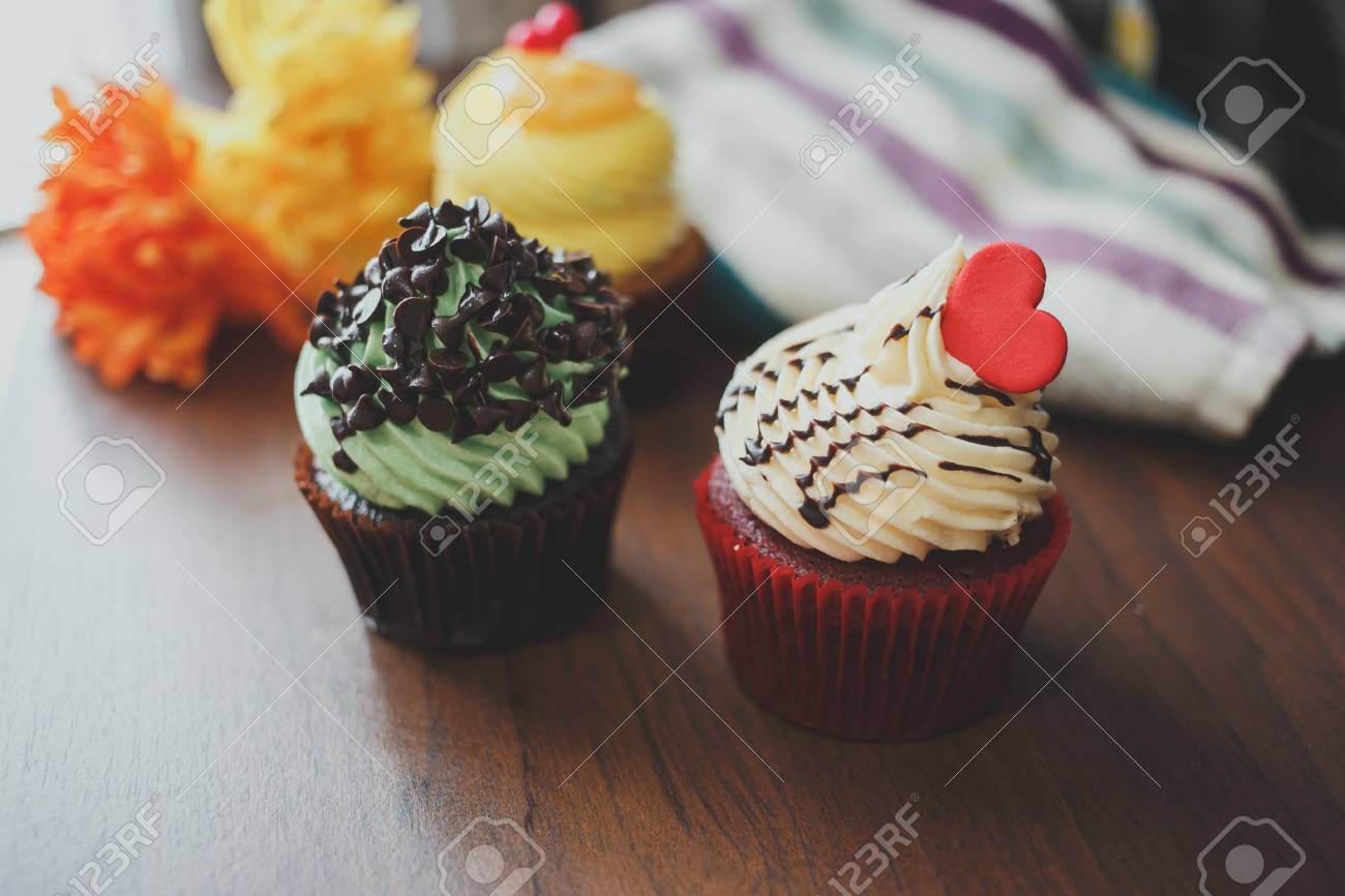 Three cupcakes of yellow, red, and green are arranged on table. - 81761025