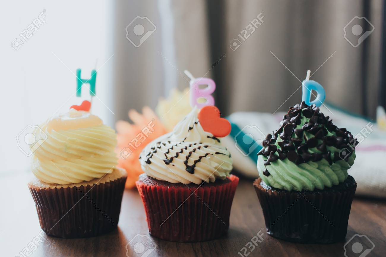 Three cupcakes of yellow, red, and green are arranged horizontally with the letter H B D, Happy Birthday - 81837215