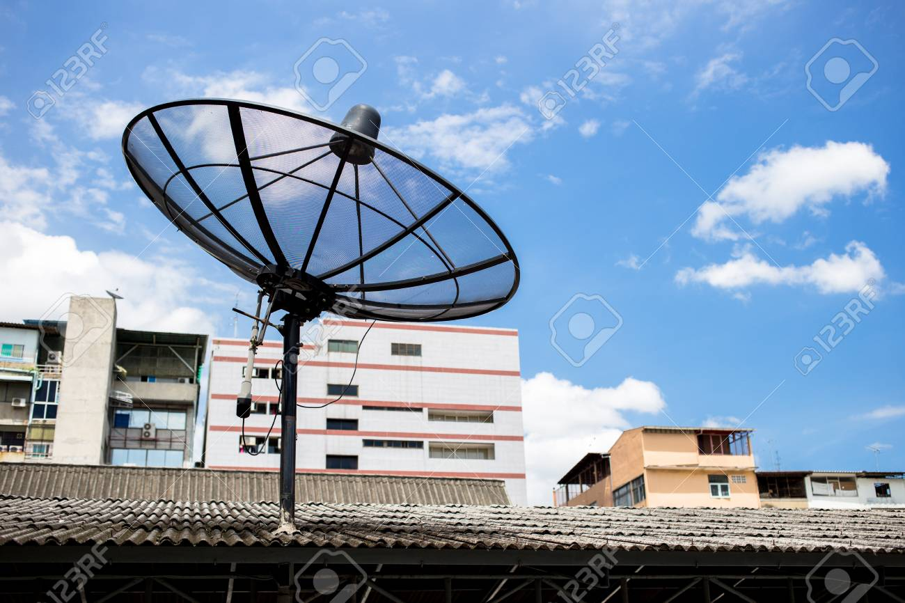 A satellite dish on the roof with a building and sky background. - 81837218