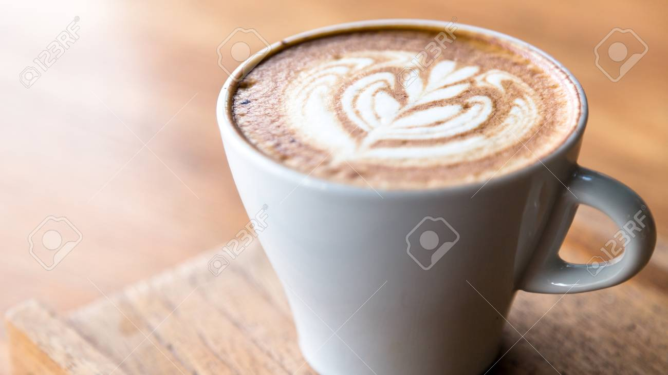 Cappuccino in white glass with wire drawing on milk froth. - 92361814
