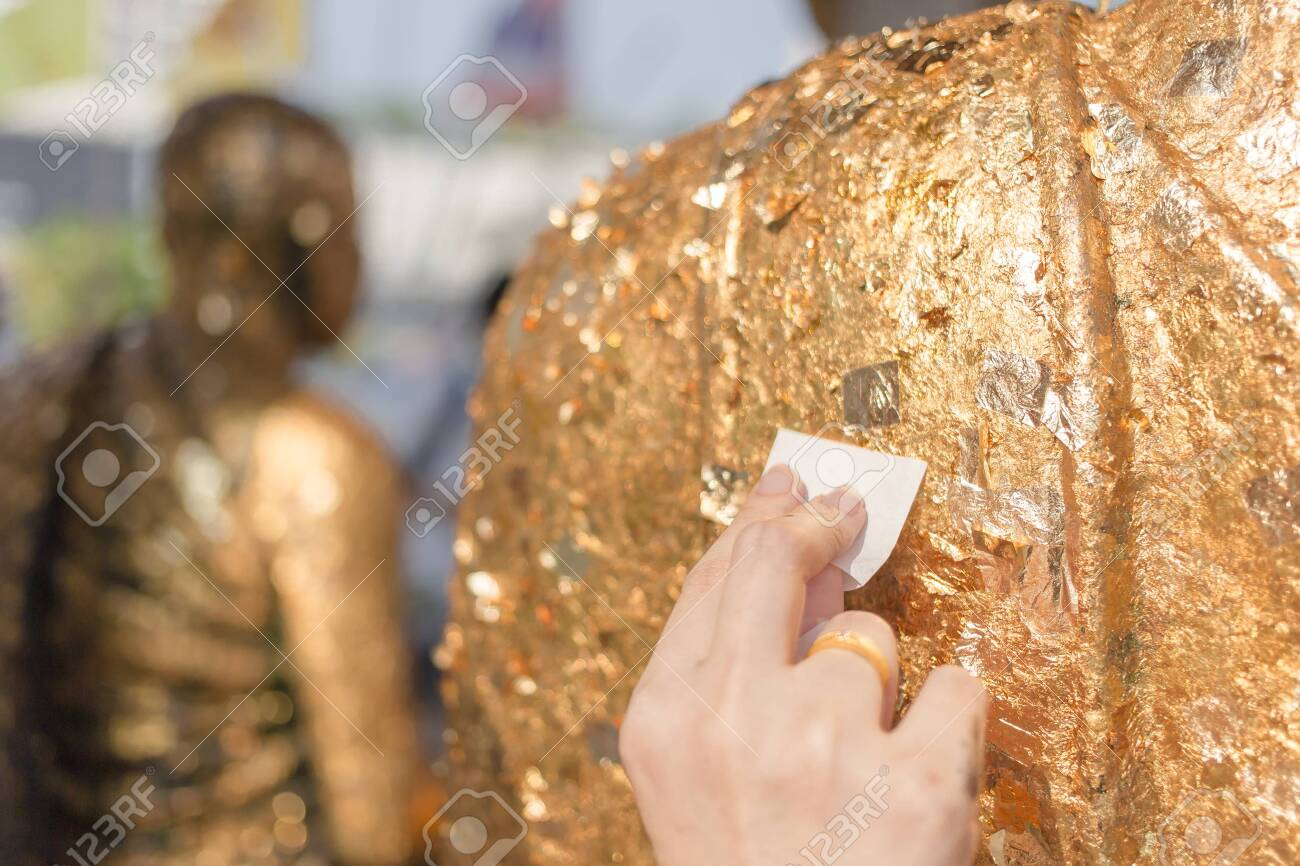 Stick gold sheet on Buddha statue. Religious ceremony of Thailand. - 142167474