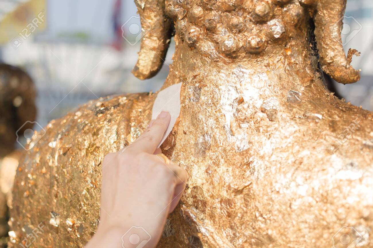 Stick gold sheet on Buddha statue. Religious ceremony of Thailand. - 142167473