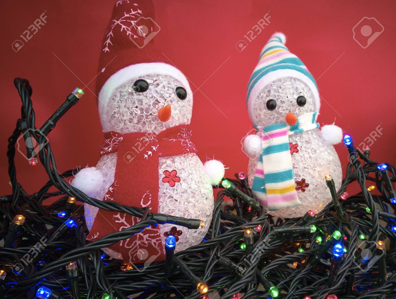 pair of little snowmen to be used as christmas decorations immersed in a sea of colored