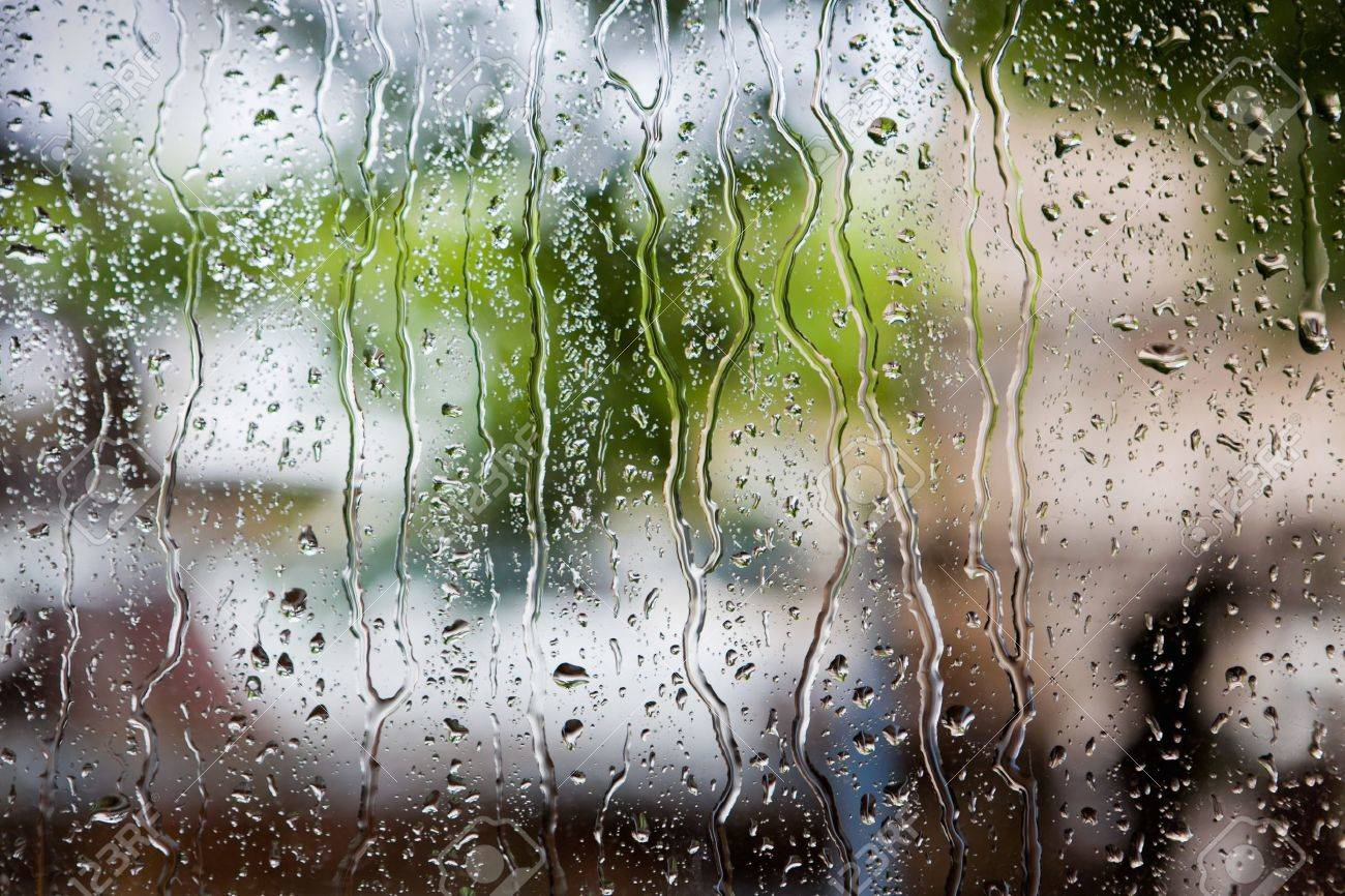 heavy rain drops on window with green background Stock Photo - 9888489