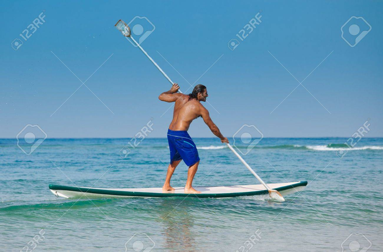 The guy with an oar on a surfboard. The beautiful brawny guy with an oar in hands on a surfboard. Stock Photo - 12448058