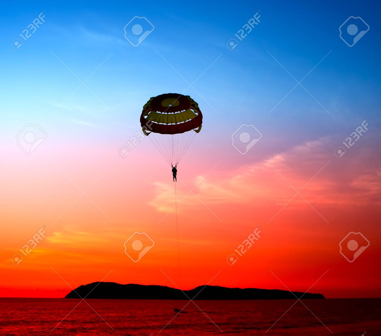 Silhouette of a parasailor at sunset Stock Photo - 10926823